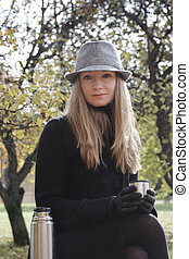 Woman in black coat and hat with cup