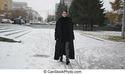 Woman in black coat walking on street