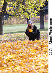 Woman in black coat with collecting leaves