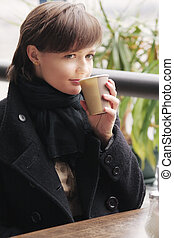 Woman in black coat with cup