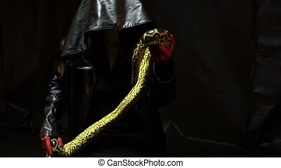 Woman in black coat with python - Footage of woman with...