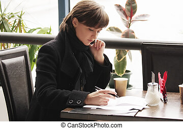 Woman in black coat working in cafe