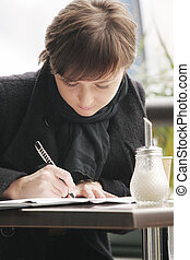Woman in black coat writing
