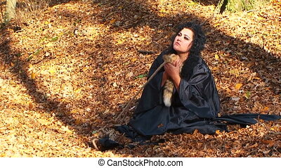 Woman In Black Cuddling A Furtail Sitting In Autumn Forest...