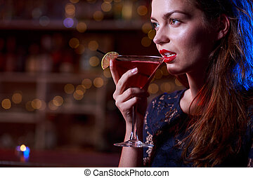 Woman in black dress drinking