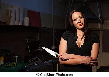 woman in black dress holding a knife restaurant 1