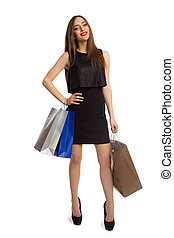 Woman in black dress holding bags