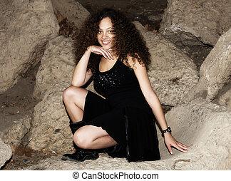 Woman In Black Dress Kneeling On Concrete Ledge