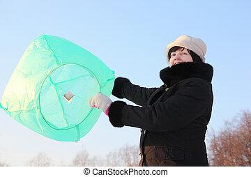 woman in black dress launching big balloon, half body, winter day outdoor