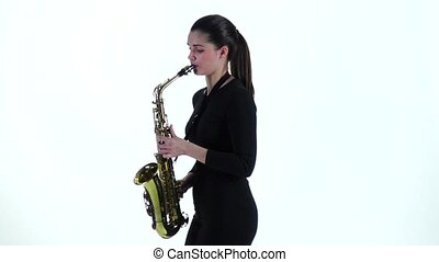 Woman in black dress plays on saxophone melody. Slow motion