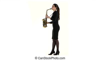 Woman in black dress plays on saxophone melody. White studio