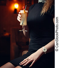 Woman in black dress sitting and holding her cocktail