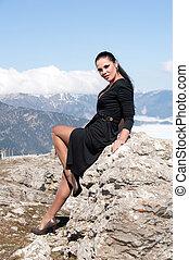 woman in black dress sitting on a rock