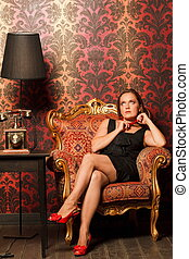 woman in black dress sitting on a vintage chair and looks up, holding a red beads. near the old phone on a wooden table and black lamp