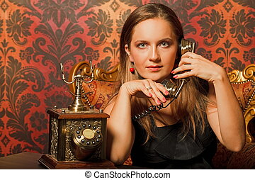 woman in black dress sitting on a vintage chair and talking on the old phone. looks into the camera