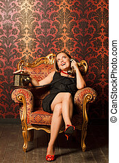 woman in black dress sitting on a vintage chair and talking on the old phone. looks up, bright emotions