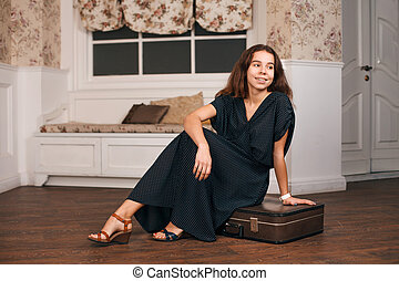 Woman in black dress sitting on her suitcase.