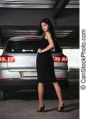 Woman in black dress stading and posing on car parking