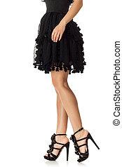 Woman in black dress standing in high heels shoes