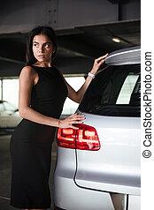Woman in black dress standing near her car