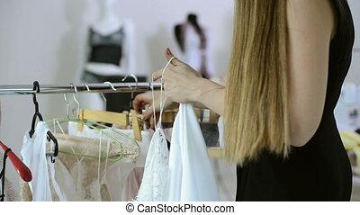 Woman in black dress standing next to rack with hangers indoors