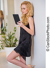 Woman in Black Dress with Tablet Leaning on Wall