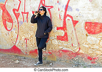 Woman in black drinking beer at a graffiti wall