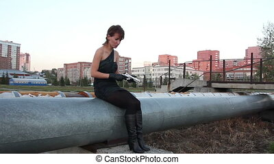 Woman in black gloves wearing a mini dress walks with a gun in her hands outdoors