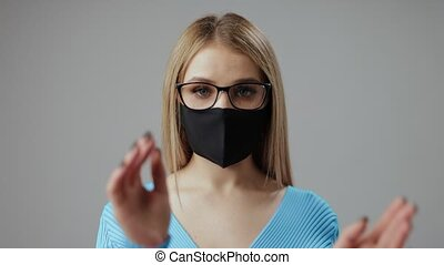 Young woman with blond hair in medical black mask holding eyeglasses for focusing over grey background. Spectacles for better sight.