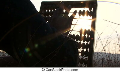 Footage at sunset - hands of woman in black moving the beads of the abacus at the field with sun shining though the counter. Blades of grass and sky in dusk on background.