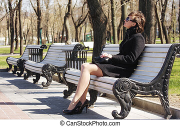 Woman in black on bench