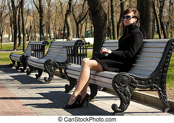 Woman in black overcoat sitting on bench