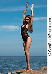 woman in black posing on sea background