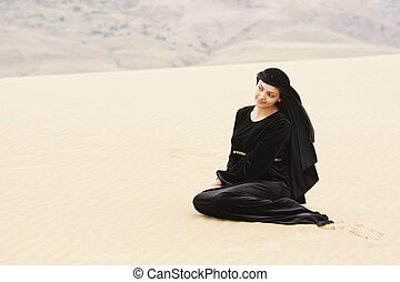 Woman in black sitting on sand
