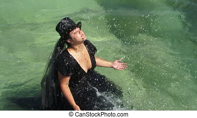 Woman In Black Splashing Water Of Pond With Hands