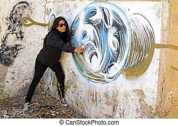 Woman in black spraying at a graffiti brick wall