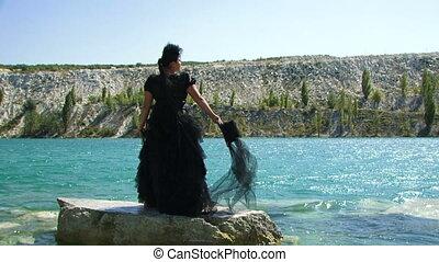 Woman In Black Standing On Rock Near Lake