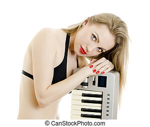 Woman in black swimsuit posing with Piano keyboard. Isolated on white.