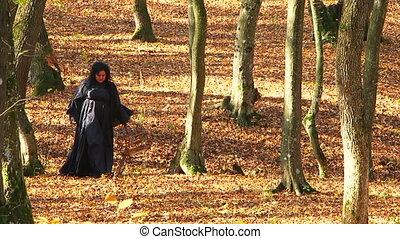 Woman In Black Walking In Autumn Forest