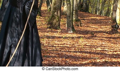 Woman In Black Walking With Fur Tail On Rope In Autumn Forest
