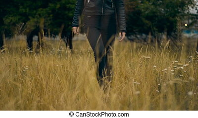 woman in black walks through a field of wheat