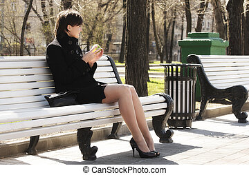 Woman in black with apple on bench