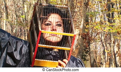 Woman In Black With Cage On Her Head In Autumn Forest