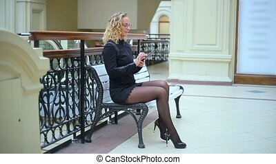 Woman in black with phone on bench