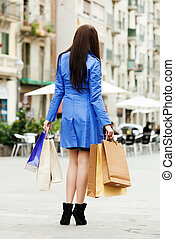 woman in blue coat with purchases