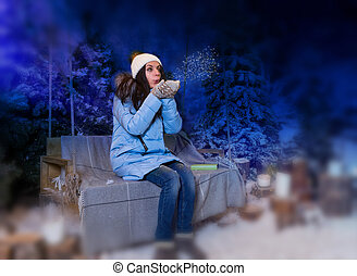 Woman in blue down jacket blows snowflakes while sitting on a swing with a blanket in the evening in a snow-covered park