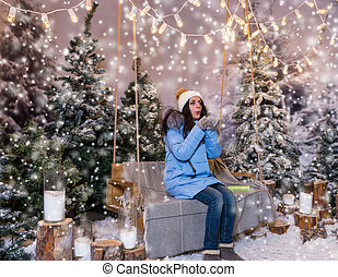 Woman in blue down jacket blows snowflakes while sitting on a swing with a blanket under the flashlights in a snow-covered park
