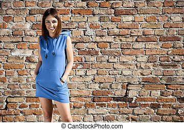 Woman in blue dress against a brick wall