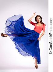 woman in blue dress kicking
