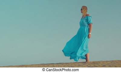 Woman in blue dress on the beach